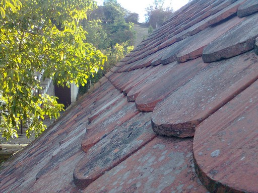 Roof tile at the far end of the photo is starting to show a slight bowing inward toward the house interior.
