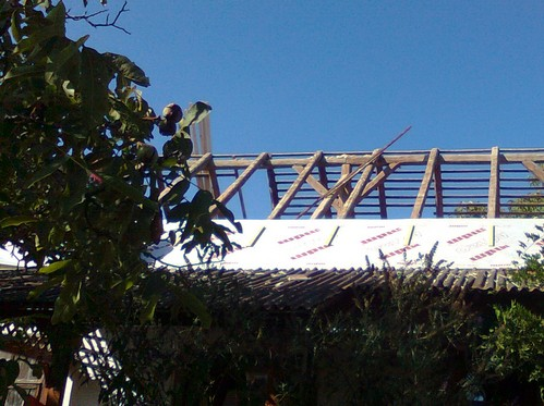 A modern vapor barrier being installed over the rafters.